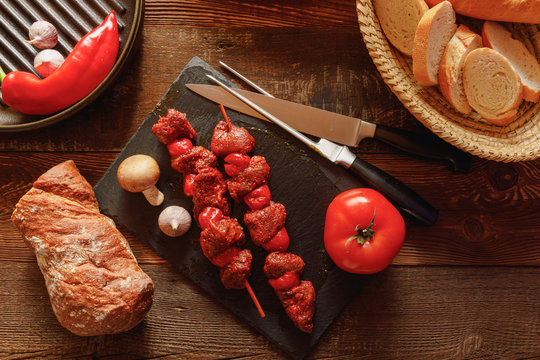 bbq skewer of beef and tomato on slate plate with garlic and mushroom bread in basket chilli pepper and cast-iron grill pan
