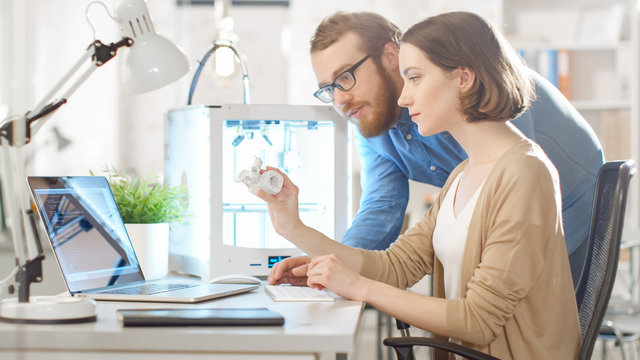 Shot of a Young Bearded Male Manager Helping to a Female Engineer Developer, who is using Laptop Computer and Expecting 3D Model. Bright Modern Office with Programmable 3D Printer.