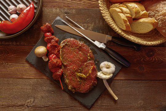 bbq beef skewer with tomato garlic mushroom and slice of spiced meat on slate plate with knife and fork bread basket red chili pepper in grill pan