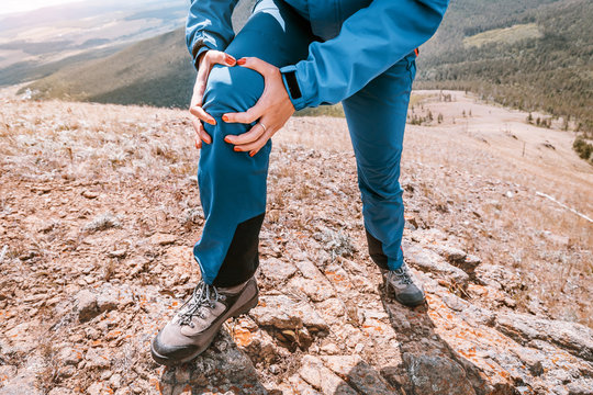 Woman is holding on to the knee joint, suffering from acute pain. Concept of injury of meniscus during a hike in the highlands