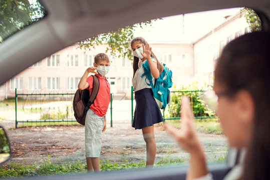 Young girl and her brother in medical masks with backpacks waving goodbye to their parents to the car while going to school during the pandemic