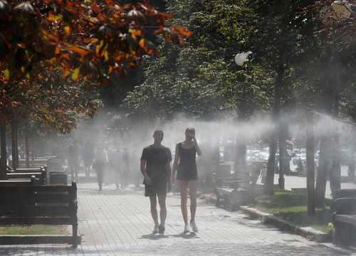 People walk through a water sprinkler on a hot summer day in central Kyiv