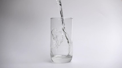 Fototapete - Pour water into drinking glass on white background in slow motion.