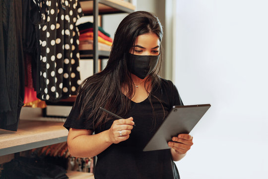 Latin woman owner of small business. Entrepreneurial woman working in her clothing store. Wearing face mask