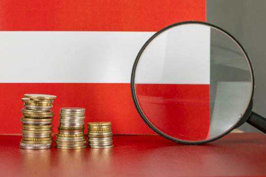 Magnifying glass and coins in front of Austria flag, country economy concept