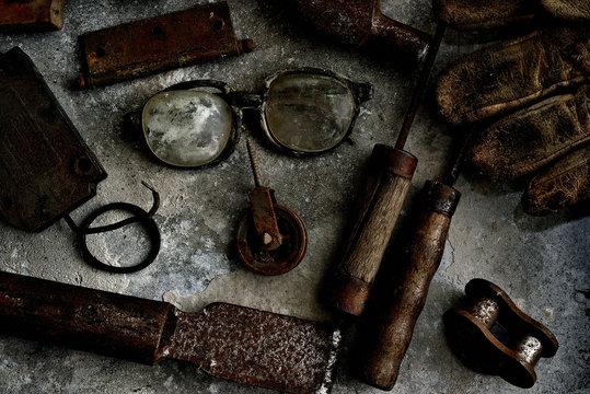 Óculos de trabalho quebrados largados no meio de ferramentas antigas