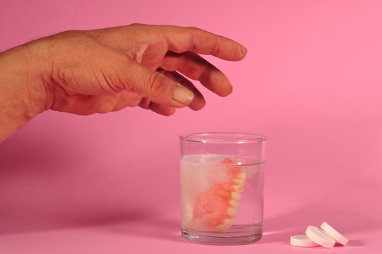 false teeth and tablets on pink background