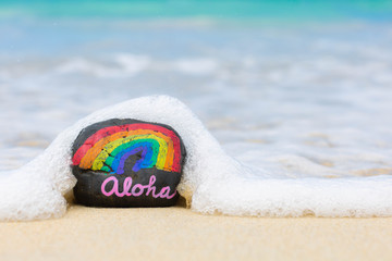 Aloha word on hawaii beach sand. Hawaiian rainbow.
