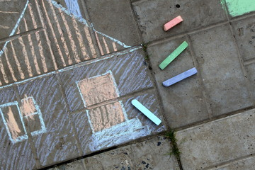 A house is drawn on the sidewalk and crayons lie nearby