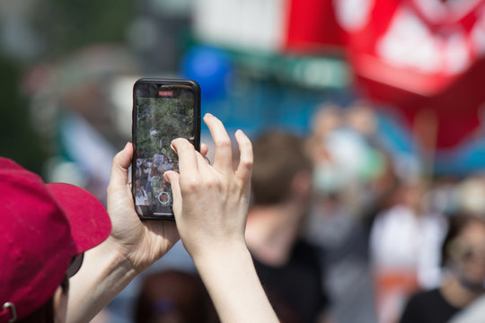 A man in a red cap is shooting something on a smartphone in the crowd. Hands holding smartphone close up