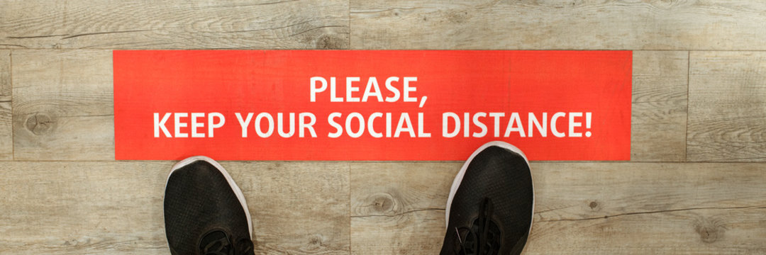 red sign board on wooden floor of store with inscription please keep your social distance and foot of man in black shoes