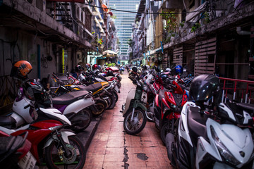 Bangkok, Thailand - March 20, 2017: Scooters parked in a narrow alley.