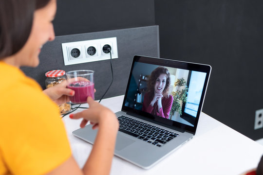 Beautiful young nutritionist woman having an online video call via laptop computer with a friend to showing detox handmade smoothie in the kitchen at home.