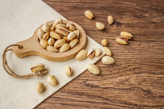 Pistachios in a small plate on a wooden table. Pistachios are healthy, vegetarian, protein-rich and nutritious foods.