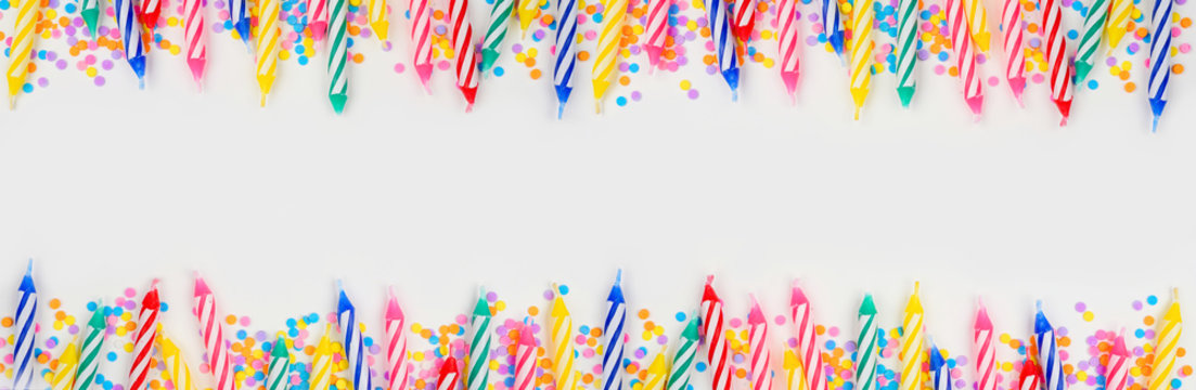 Colorful birthday cake candles with candy sprinkles. Top view banner with double border on a white background. Copy space.