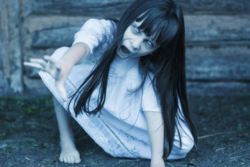 Photo sur Plexiglas Doux monstres Scary ghost girl pulling with her hand and crept on the ground