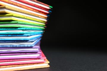 Edukacja - podręczniki w kolorowych okładkach ułożone w stos, kolory tęczy