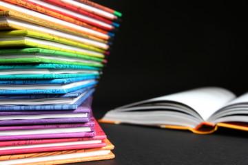 Edukacja - lektury szkolne, książki ułożone jedna na drugą w kolorach tęczy na ciemnym tle