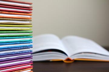 Kolorowe książki ułożone w stos, otwarta książka w tle