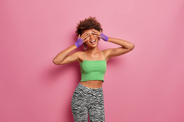 Horizontal shot of positive carefree slim woman covers face with hands, smiles broadly, keeps eyes shut, wears sport clothing, goes in for sport regularly, being energetic, poses over pink background