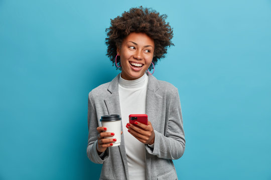 Successful Afro American entrepreneur in formal wear holds mobile phone, orders lunch online, drinks takeaway coffee, checks message, makes new appointment, looks with broad shining smile aside