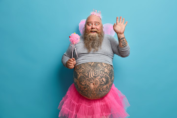 Horizontal positive man animator on childrens party, dressed in fairy costume, waves palm in hello gesture, has good mood during holiday, being kind magician, has big tattooed belly, blue background Wall mural