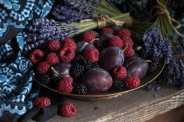 Raspberries, blackberries, plums in a bowl and bunches of lavender on a wooden background. Fragment, blur, selective focus.