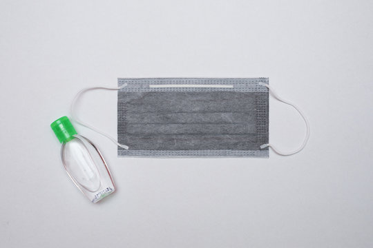 Coronavirus prevention using 3 ply surgical mask and hand sanitizer. Top view with white background.