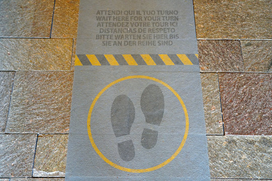 """Footprint with the text """"WAIT HERE FOR YOUR TURN'' in six languages-social distance"""