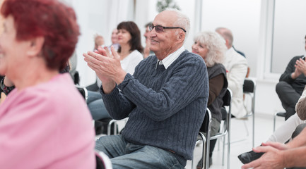 a group of senior citizens applaud in the conference room