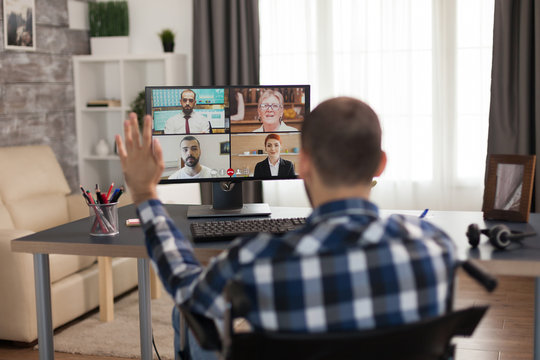 Businessman in wheelchair waving during a video call with business partners. Young immobilized freelancer doing his business online, using high technology, sitting in his apartment, working remotely