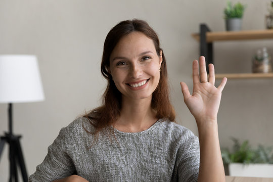 Headshot portrait of smiling young Caucasian red-haired woman wave greeting talk on video call, happy millennial female have virtual digital webcam conference conversation, new technology concept