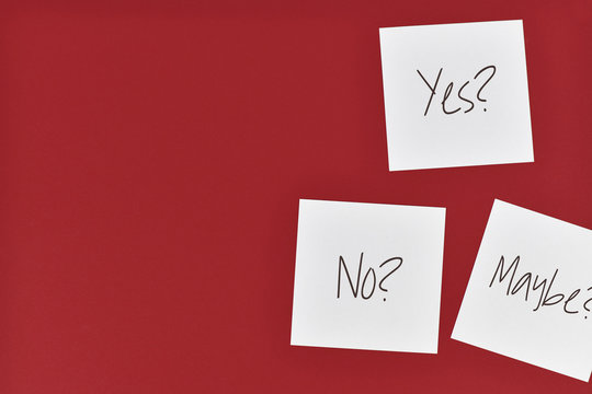 Decision making concept with white paper notes with words 'Yes?', 'No?' and 'Maybe?' on dark red background with empty copy space
