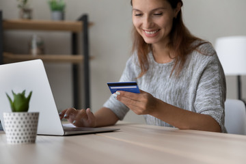 Crop close up of happy young woman sit at desk pay online on laptop using credit card, smiling millennial female client customer shopping on internet, make secure web payment purchase on computer