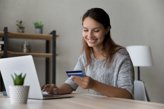 Smiling millennial Caucasian female sit at table at home make online payment purchase using credit card, happy young woman shopping on internet, pay on web with secure banking service system on laptop