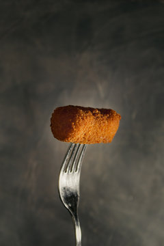 Homemade traditional spanish croquettes on a fork with dark background. Tapas food.