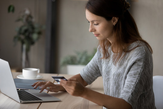 Young Caucasian woman sit at table make online payment or purchase using secure web banking system on computer, millennial female shopping on internet, pay bills with credit card on laptop on web