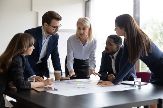 Senior woman team leader explaining marketing plan details to young diverse employees on briefing in office, millennial businesspeople listening attentively to mature female trainer or coach
