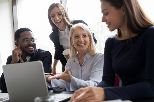Pleasant mature woman qualified employee explaining business task details to younger colleagues, happy aged lady team leader showing diverse millennial staff solution of problem on computer screen