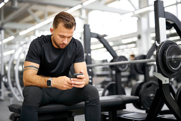 young tired fitness man using smartphone in gym. male in black sportswear have rest after...