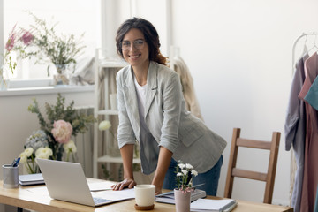 Beautiful young businesswoman in glasses looking at camera, posing for photo in modern creative office. Portrait of happy millennial fashion designer enjoying workday alone in atelier showroom.