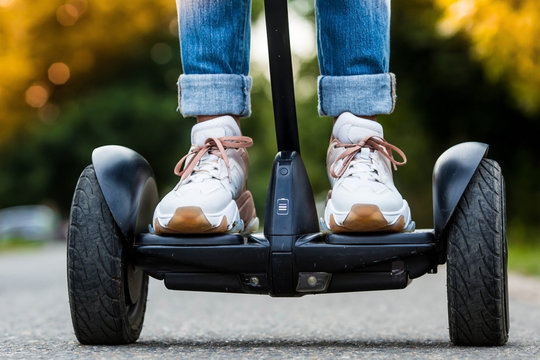 A young hipster girl driving a hoverboard outdoors in a Park, an active woman balancing on a modern electric Board, the concept of the future, alternative transport, ecology and the environment.