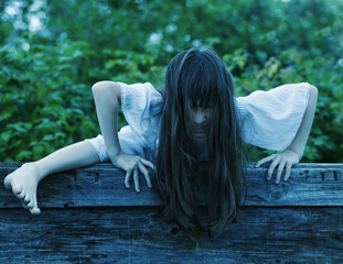 Photo sur Plexiglas Doux monstres Scary ghost girl climbs out of the well