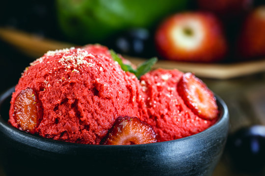 vegan strawberry ice cream, red ice cream with fruits, served in handmade clay pot