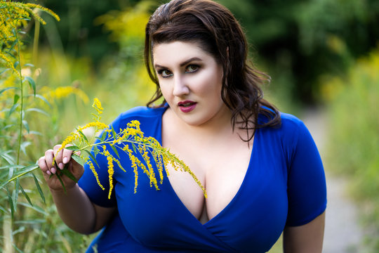 Sexy plus size fashion model in blue dress with a deep neckline outdoors, beautiful fat woman with big breasts in nature