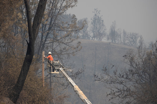 Man fixes damaged telephone line in aftermath of LNU Lightning Complex Fire in Spanish Flat, California