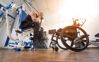 Disabled man doing strength exercises separate from the wheelchair.
