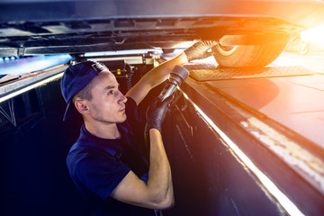 Car mechanic examining car suspension of lifted automobile at service station
