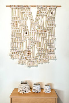 Hand crafted macrame wall decoration with wooden elements. hanging on a wall, three hand made candle holders are place below on the shelf.