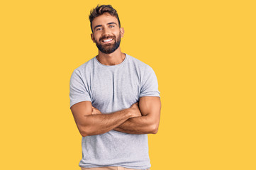 Young hispanic man wearing casual clothes happy face smiling with crossed arms looking at the camera. positive person.